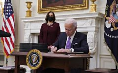President Joe Biden signs an executive order after speaking during an event on his administration's COVID-19 response with Vice President Kamala Harris, left, in the State Dining Room of the White House in Washington, D.C., on Thursday, Jan. 21, 2021. (Al Drago/Pool/Abaca Press/TNS)
