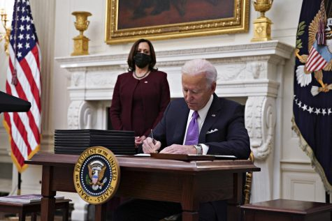 President Joe Biden signs an executive order after speaking during an event on his administration