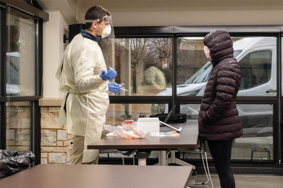 Jason Suchon, an employee of Southern Illinois Hospital (SIH), puts on his gloves, mask, face shield and apron to test a resident of the SIU dorms Monday Jan. 25, 2021, at Becker Pavilion near Campus Lake in Carbondale, Ill.