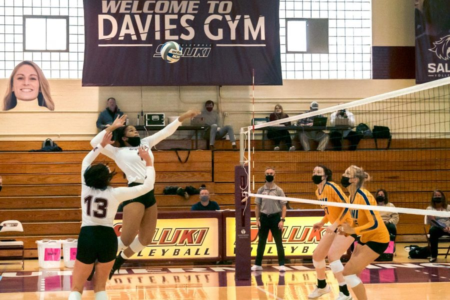 """SIU middle Blocker, Imani Hartfield (16), leaps to meet the ball as it falls mid-air Sunday, February 21, 2021, at Davies Gym in Carbondale, Ill. Hartfield is a freshman studying biology in the pre-med track with a season high of 14 kills in a game. """"A kill is when you hit the ball and the other team isn't able to pick it up and bring it back over,"""