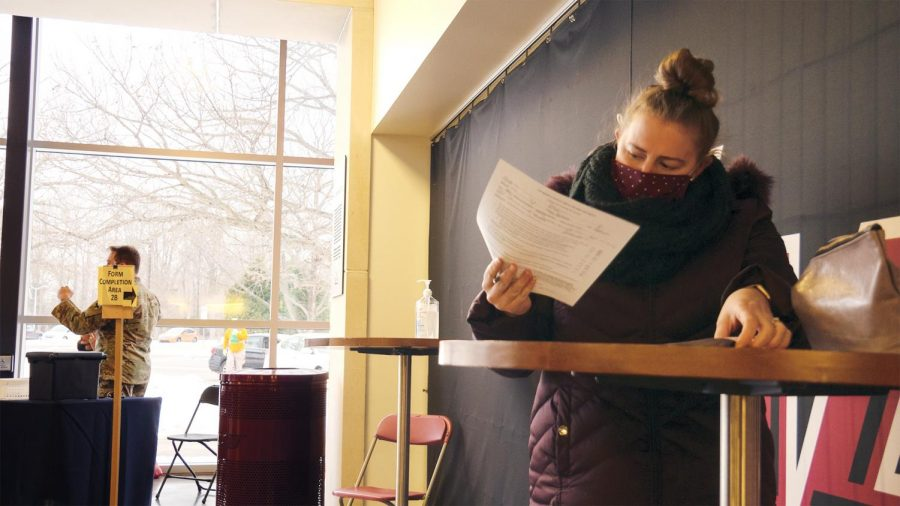 """Abigail Moberly, a Carbondale local, puts the last touches on paperwork for her COVID-19 vaccination Thursday, Feb. 11, 2021, in Carbondale, Ill. """"I work in education so I'm a part of that group. So ya know, I've been waiting and I said, 'As soon as it's ready, I'm ready,'"""" Moberly said. In partnership with the Jackson County Health Department, SIU offered a vaccination clinic for all qualified citizens."""