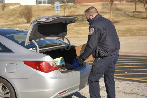Carbondale police lend a hand by helping handout boxes of fresh fruits and vegetables on Friday, Feb. 5, 2021, outside the Banterra Center at SIU.
