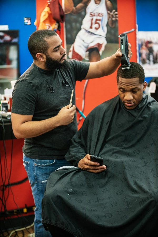 Quivon Bledsoe cuts Ryan Reed's hair Thursday, Feb. 11, 2021, in Carbondale, Ill. Bledsoe has been a barber at Kampus Kuts since 2009 and is a Doctoral Candidate for the Rehabilitation Council program at SIUC.