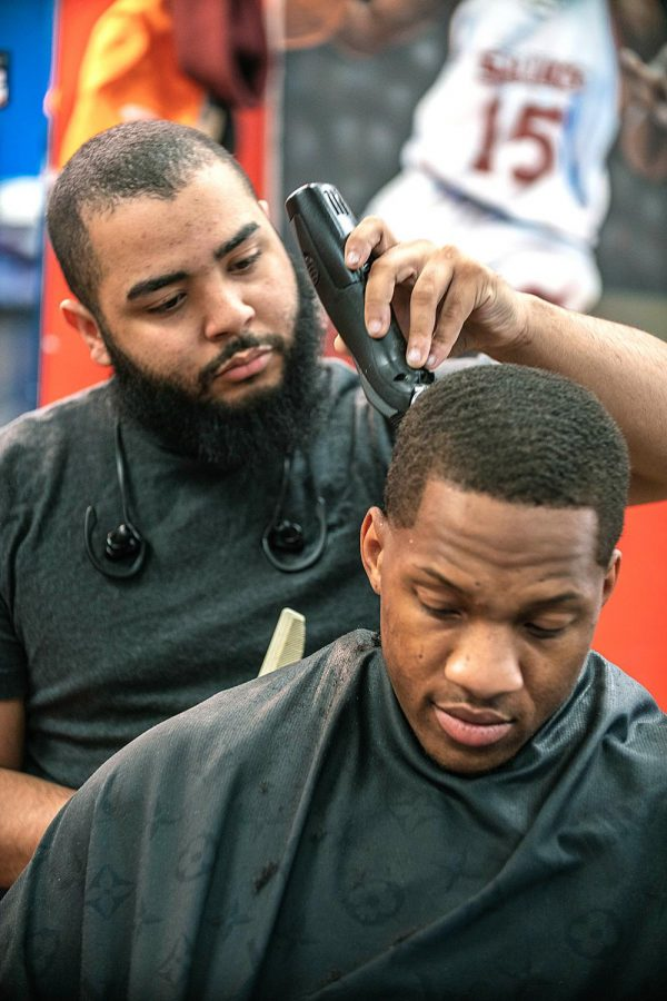 Quivon Bledsoe trims Ryan Reed's hair Thursday, Feb. 11, 2021, in Carbondale Ill. Inside Kampus Kuts, are several paintings and art pieces that showcase Carbondale's environment and culture, including several basketball players from SIU.