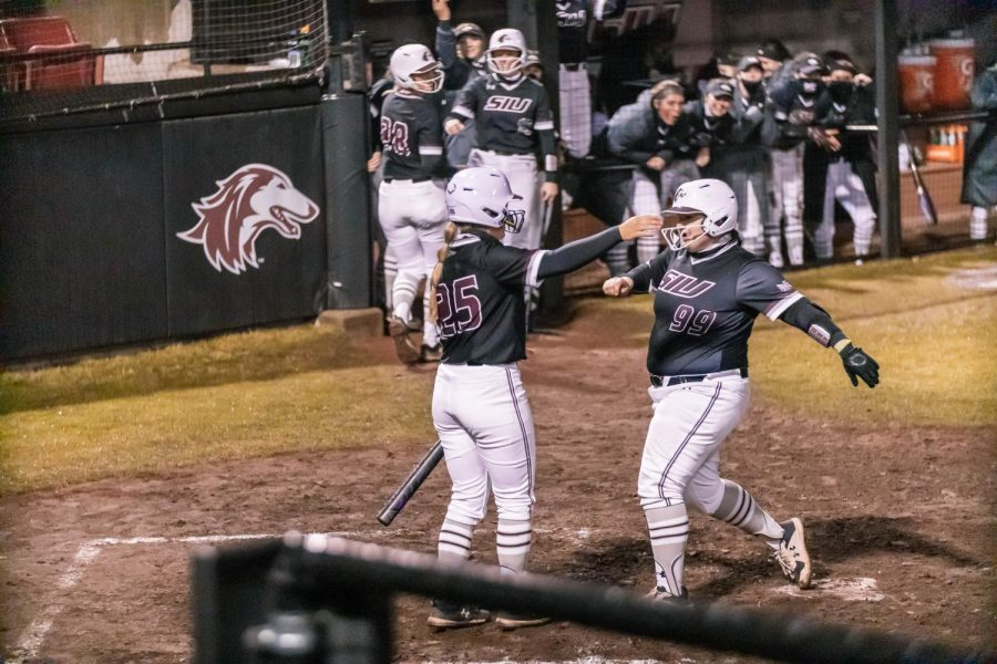 Katelyn Massa (99) celebrates with her teammates after scoring a home run in a game against Austin Peay State University Friday, Feb. 26, 2021 at SIU.