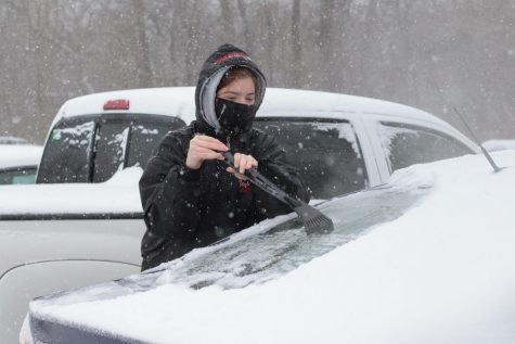 Cassandra Jett clears snow and ice off of her car Monday, Feb. 15, 2021, in Carbondale, Ill.