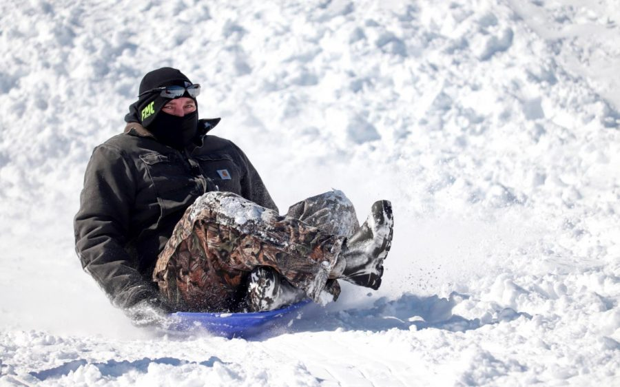 A man sleds down a hill on the SIU campus Feb. 16, 2021, in Carbondale, Ill. Though it would have been easy to stay indoors during the wintery weather, many members of the community found themselves outside enjoying the snow.
