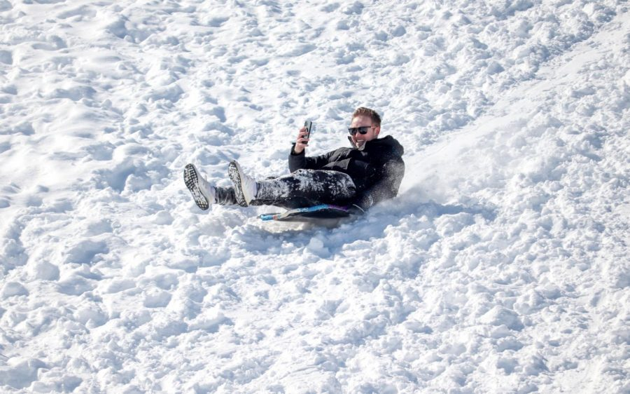 An SIU student records a video as he sleds down a slope Feb. 16, 2021, in Carbondale, Ill. Many students took advantage of the day off of school by going outdoors and sledding on campus by the Banterra Center.