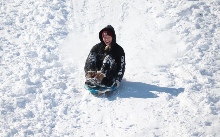 A girl slides down a hill outside of the Banterra Center Feb. 16, 2021, in Carbondale, Ill. Community members in Carbondale enjoyed the day off of school by hitting the hills near the Banterra Center on the SIU campus for some sledding.