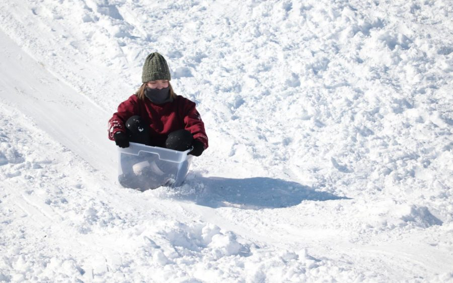 Student slides down a snowy hill in a plastic bin Feb. 16, 2021, in Carbondale, Ill. Though the snow shut down roads and schools, it made for perfect sledding grounds on SIUs campus on Tuesday.