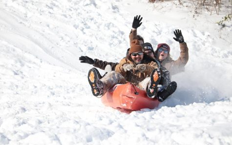 Students sled down a hill in a kayak Feb. 16, 2021, in Carbondale, Ill. Many students had to get creative to find materials to sled down the hills during the snow day and these men chose the successful idea of using a kayak.