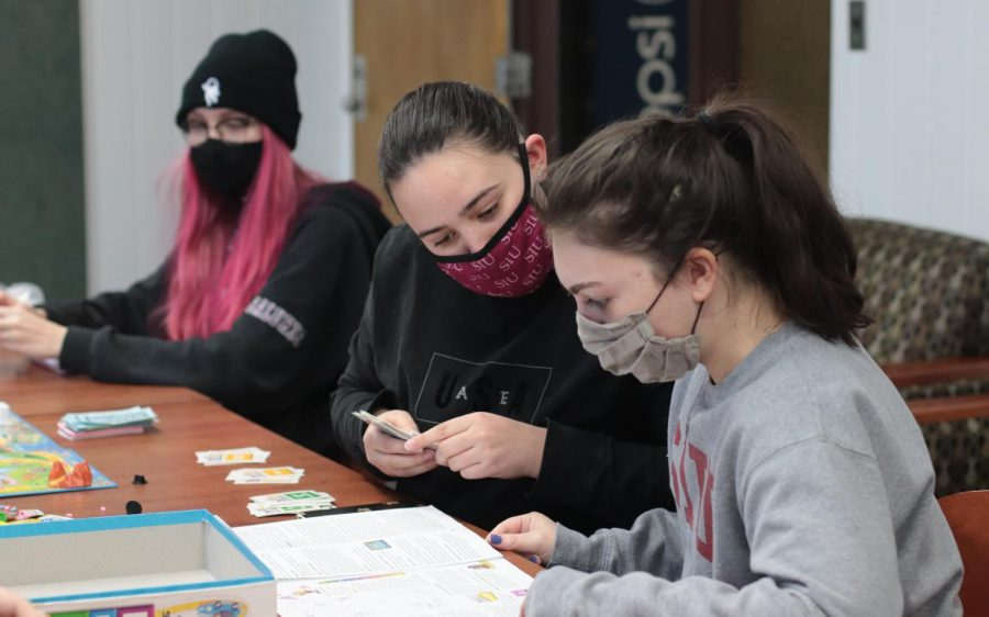 SIU students, Amanda Rhodes (left) and Maggie Loesch (right) read directions for a board game Feb. 16, 2021, in Carbondale, Ill.