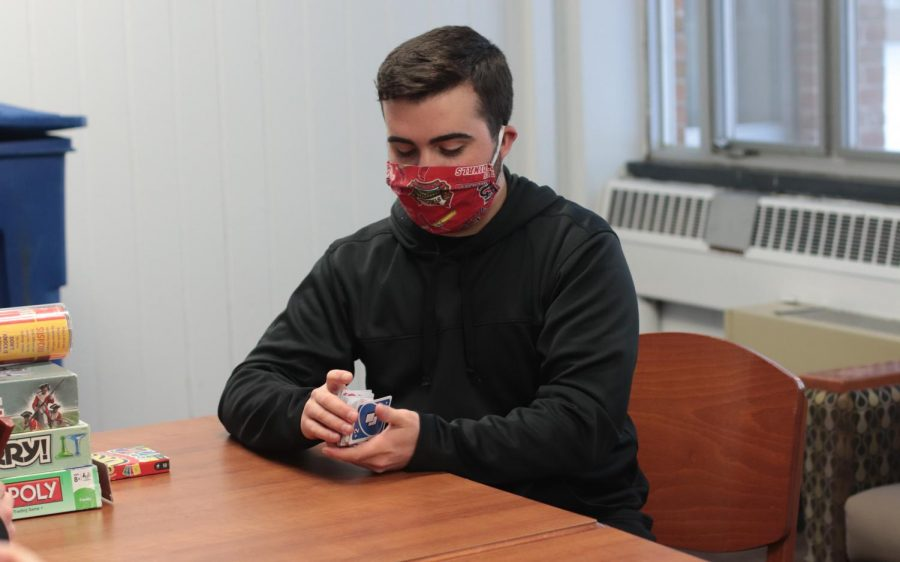 Resident assistant, Tyson Lukrofka, shuffles a deck of Uno cards Feb. 16, 2021, in Carbondale, Ill. Due to the campus closure for the weather, the resident assistants at Brown Hall on West Campus organized a game day for the students to engage in on their day off of school.
