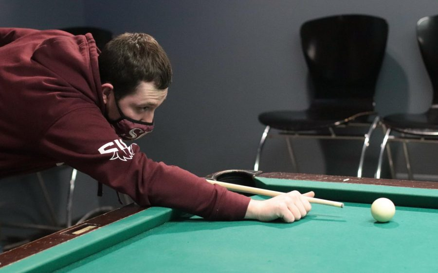 SIU student, Colton Warnes plays pool at Mae Smith Feb. 16, 2021, in Carbondale, Ill. While trying to get out of the cold, Warnes and his friend Evan Strauch stayed inside and played a game of pool.