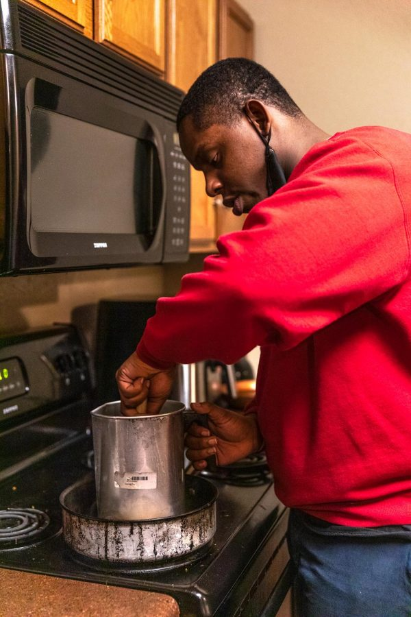 """Dre James, owner of Victoria Candle Co., melts a pitcher of wax on his stove Feb. 21, 2021, in Carbondale, Ill. James said that he uses aDouble boiling method so that the wax doesn't burn from the heat. He sources his wax from an American company that sells soy wax. """"The first candles I made, I went to Dollar Tree and bought the candles that were already made and remelted them and it didn't turn out too well. So that's when I really started to research candle making,"""" James said."""