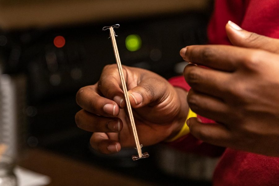 Dre James, owner of Victoria Candle Co., holds up a wooden wick Feb. 21, 2021, in Carbondale, Ill.