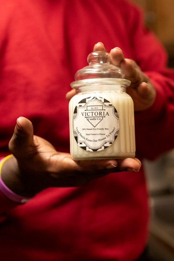 """Dre James, owner of Victoria Candle Co., holds up one of the first candle vessels that he ever used Feb. 21, 2021, in Carbondale, Ill. """"This was one of the candles from the very first batch that I made, and I never lit it and held onto it as a reminder of where Victoria Candle Company started and as motivation to keep me going,"""