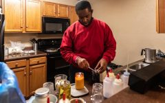 "Dre James, owner of Victoria Candle Co. works on candle orders in his apartment Feb. 21, 2021, in Carbondale Ill. -	""Every month my customer basis is increasing so I'm obviously doing something right,"" James said. He started his business in 2019 after having a dream about pouring candle wax. -	""I just joined the Carbondale Chamber of Commerce and the president ordered a candle, so I just got done making his,"" James said."