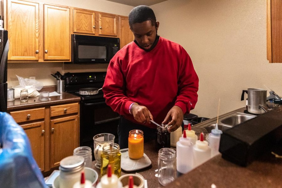 """Dre James, owner of Victoria Candle Co. works on candle orders in his apartment Feb. 21, 2021, in Carbondale Ill. -""""Every month my customer basis is increasing so I'm obviously doing something right,"""" James said. He started his business in 2019 after having a dream about pouring candle wax. -""""I just joined the Carbondale Chamber of Commerce and the president ordered a candle, so I just got done making his,"""" James said."""