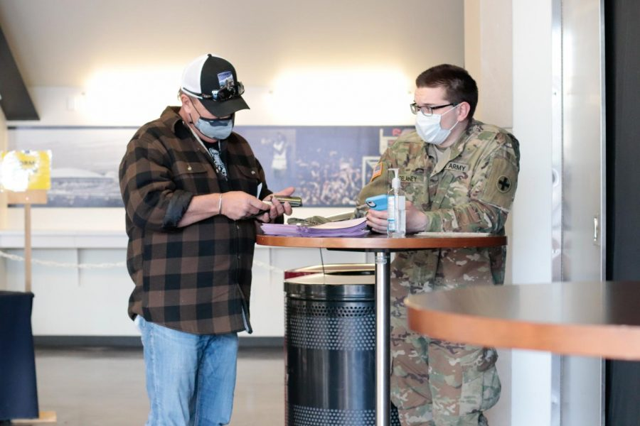 """David Craig answers a health survey before he receives his COVID-19 vaccination Feb. 20, 2021, in Carbondale, Ill. """"I'm like everybody else, I just think you ought to have it,"""" Craig said."""