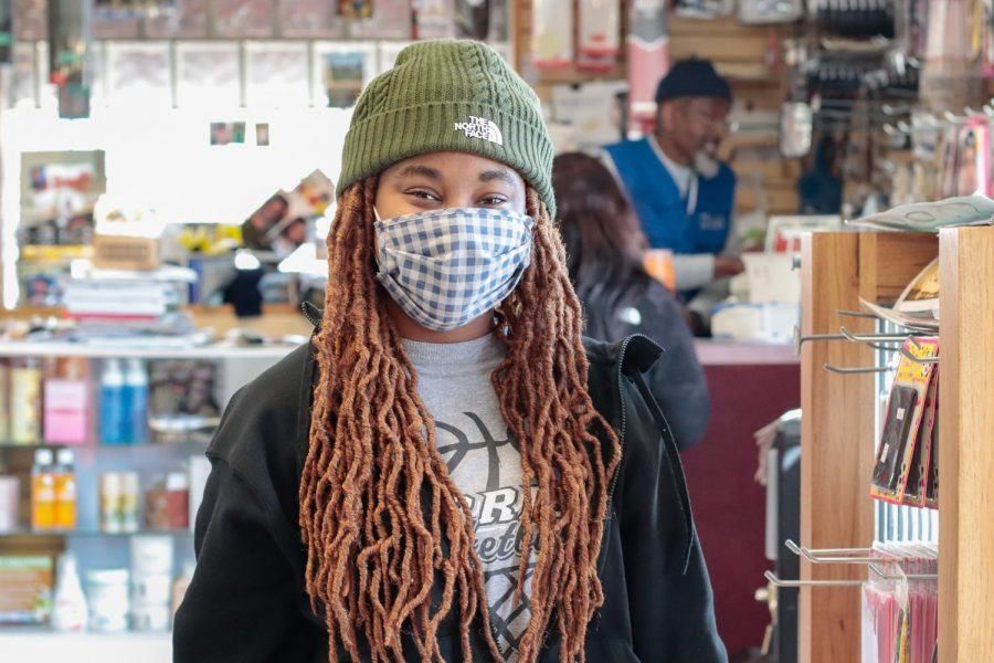 """Tyra Coleman poses in Rahim's Beauty Supply Feb. 22, 2021, in Carbondale, Ill. She said that she enjoys changing her hair and trying new hair styles. """"It makes me feel confident because I look good. I like getting my hair done,"""" Coleman said."""