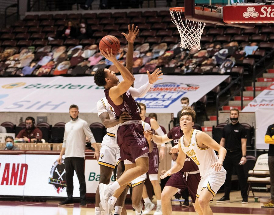 Dalton Banks (3) tries a jump shot in front of undefended hoop during the game against Valparaiso Crusaders on Monday, Feb. 22, 2021, at the SIU Banterra Center in Carbondale, Ill. SIU won the game by 3 points, scoring 67-64.