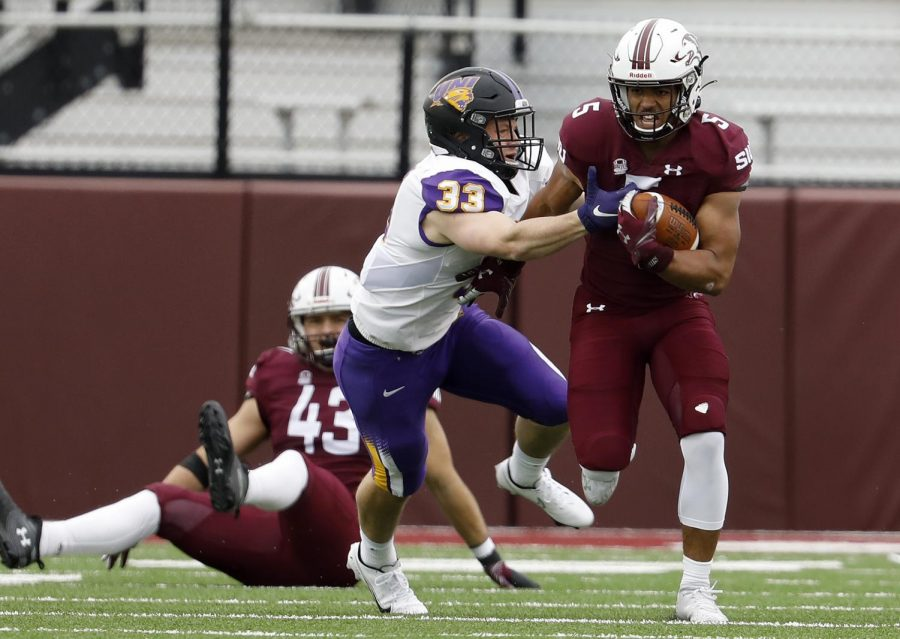 Salukis running back Justin Strong tries to get past the reach of Panthers defender Nick McCabe during the SIU's 17-16 win at Saluki stadium on Saturday, March 13, 2021.