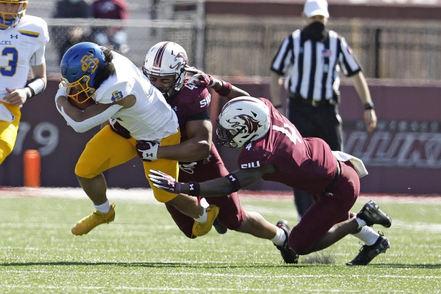 Saluki defenders, PJ Jules, 4, and Raquan Lindsey, 44, make a tackle during Saturday's game at Saluki Stadium on March 20, 2021. SIU lost to South Dakota State by the score of 44-3.