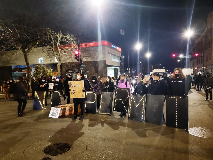 """Oscar Sanchez stands on a coffin to speak in the intersection of Milwaukee, Belmont, and Diversey Avenues in Chicago, Ill. on March 4, 2021. """"My grandpa died in December because he had damaged lungs. That's not right,"""" Sanchez said."""