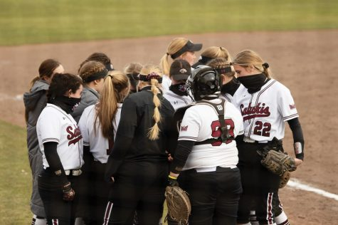 SIU players huddle up during a  game against Northern Kentucky University on Friday, Mar. 5, 2021 at Charlotte Softball Stadium in Carbondale, Ill.