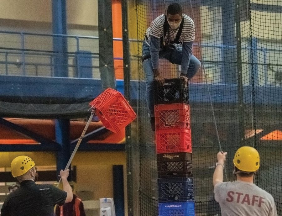 Kylen Lunn balances his body on a tall pile of crates before attempting to add one more crate to the stack during the Crate Stack Challenge held on Tuesday March. 16, 2021, at Recreational Center, Carbondale Ill.