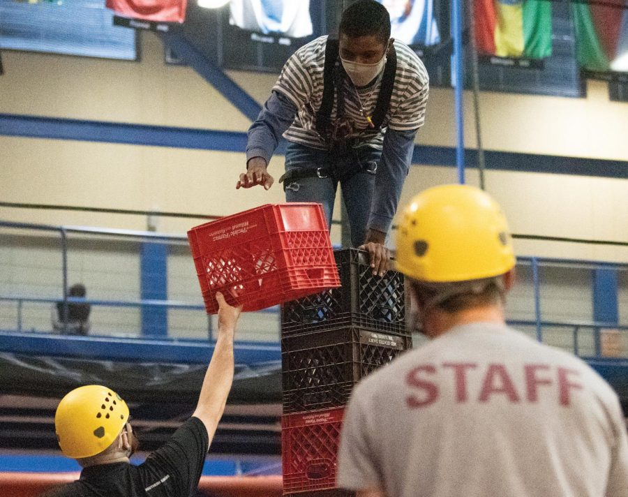 Kylen Lunn receives a crate from Rec staff on his one hand while supporting his body against the crate pile with the other hand during the Crate Stack Challenge held on Tuesday March. 16, 2021, at Recreational Center, Carbondale Ill. The program lasted for 3 hours starting from 6:00 PM.