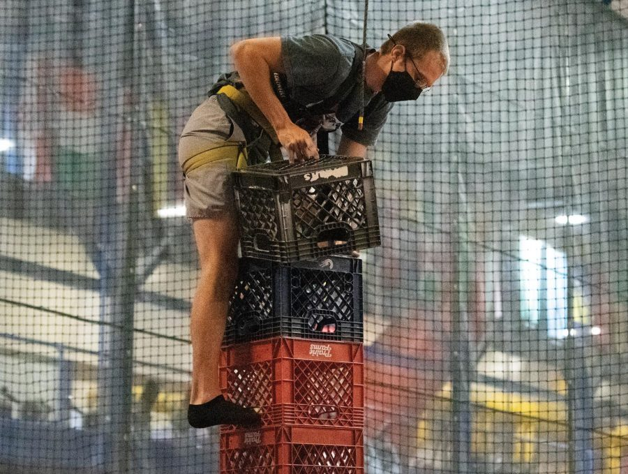 Caleb Meator leans his body to align his center of gravity while attempting to add another crate to his collection during the Crate Stack Challenge held on Tuesday March. 16, 2021, at Recreational Center, Carbondale Ill.