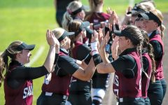 The SIU Salukis softball team gives each other high fives before the game against Drake University on Sunday, March 21, 2021 at SIU.