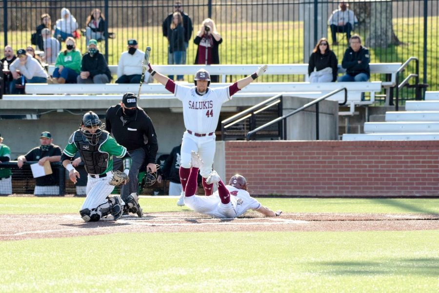 Brad Hudson (4) slides into home plate for another steal during the fourth inning against Marshall University at Itchy Jones Stadium on March 20, 2021 in Carbondale, Ill.