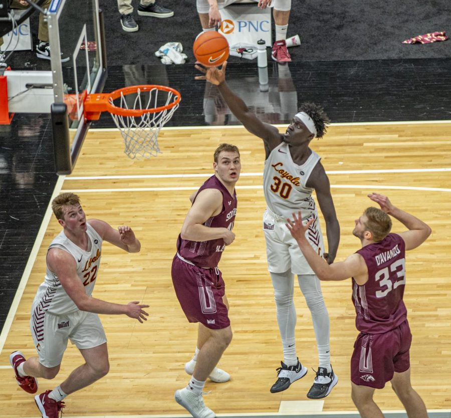 Both Kyler Filewich and Anthony D'Avanzo watch as Loyola's Aher Uguak goes up for the score during the Salukis' 49-73 loss against Loyola in the Arch Madness tournament on Friday, March 5, 2021 at the Enterprise Center in St. Louis, MO.