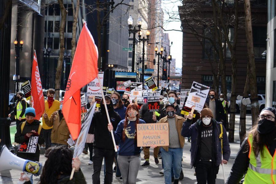 Supporters of a unionization effort at an Amazon warehouse in Alabama march on the sidewalk for a Day of Solidarity on March 20, 2021, in downtown Chicago, Ill.