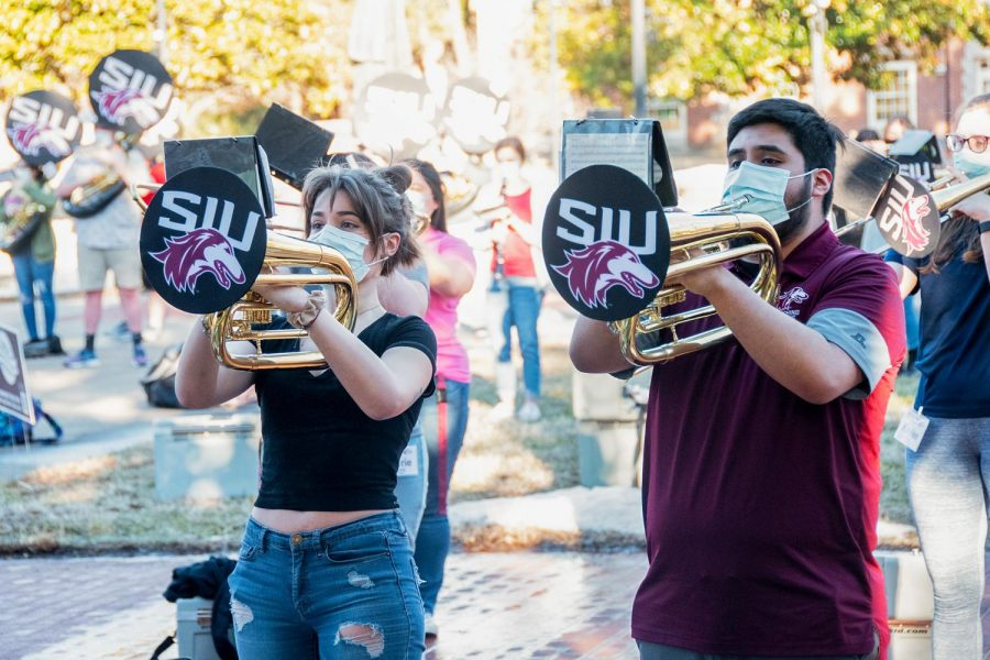 """Peyton Schnurr, a senior art major and Luiie Barrera, a sophomore mathematics major, play """"All Star"""" by Smashmouth to get ready for their upcoming performance at the next football game on Feb. 22, 2021, in Carbondale Ill."""