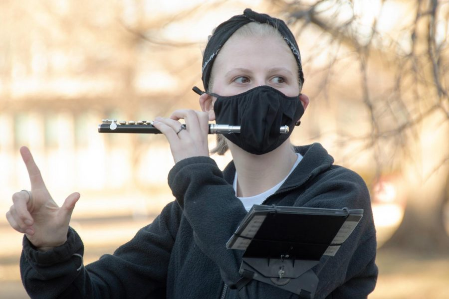 Allyson Peters, a junior majoring in dentistry, practices the piccolo with the marching band outside Shryock auditorium on Feb. 22, 2021, in Carbondale, Ill.