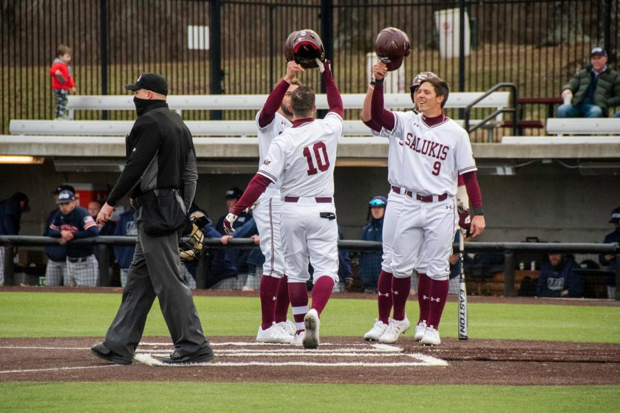 Saluki players congratulate each other after a home run hit by Vinni Massaglia, SIU outfielder, against Tennessee Martin on Friday Mar. 5 2021 at Itchy Jones Stadium in Carbondale, Ill.