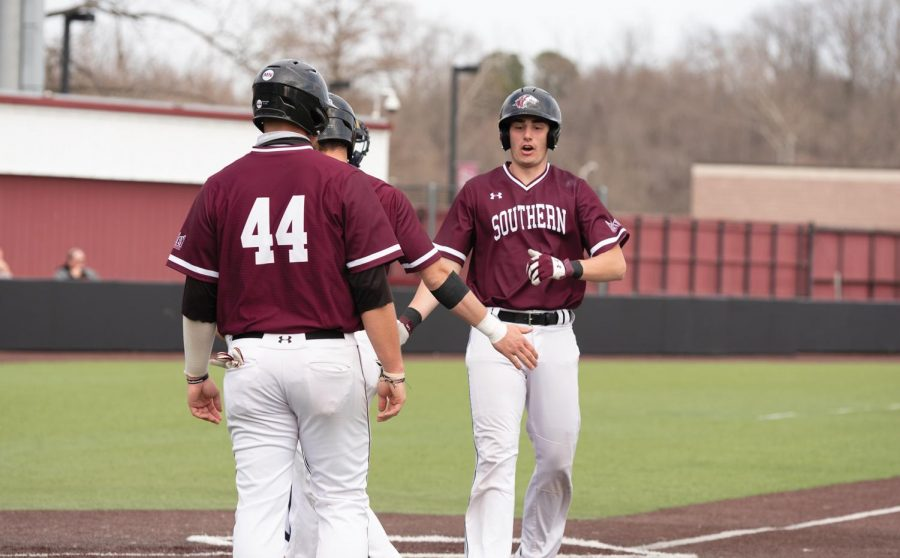 Tony Rask (18) gives his teammate a high five during the Salukis home game against the University of Tennessee at Martin on Saturday, Mar. 6, 2021 at Itchy Jones Stadium in Carbondale, Ill.