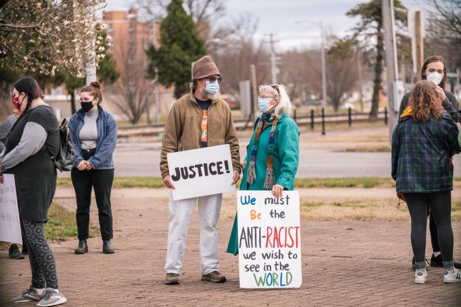 Dennis Conolly, left, and Georgean Hartzog stand with their signs ready before the protest on the one year anniversary of Breonna Taylor's death Saturday, March 13, 2021 in Carbondale, Ill.