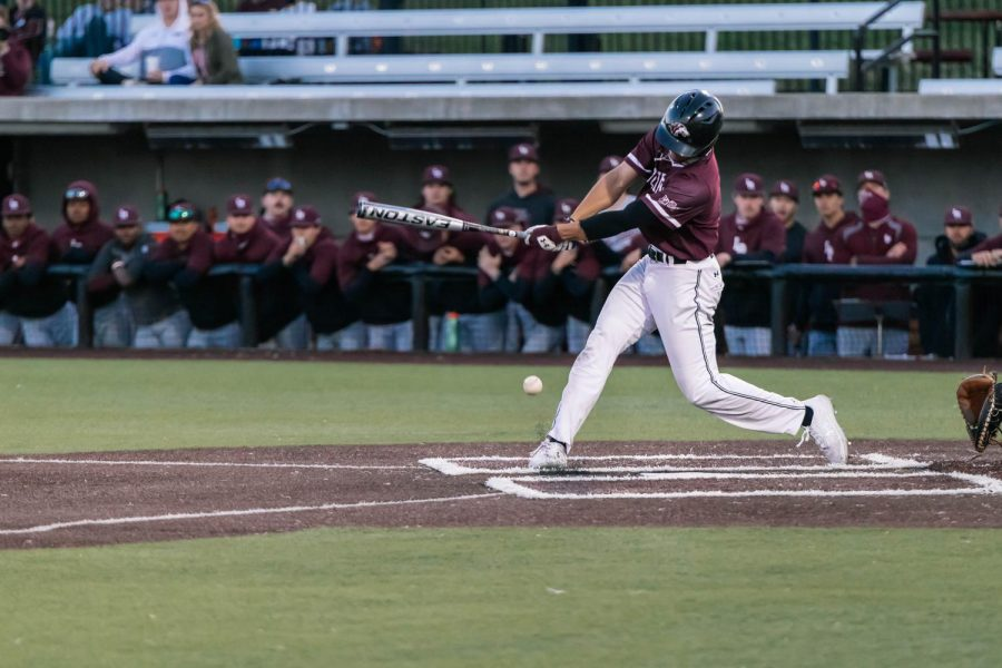 Evan Martin (2) hits a double in game one against University of Arkansas Friday, March 26, 2021 at SIU. With all three bases loaded from walked batters, Martin's hit scored two for the Salukis.