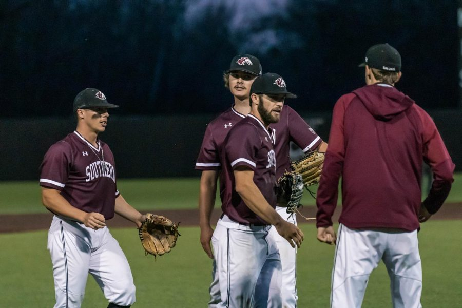 The Salukis congratulate Tristan Peters (6) in game one against University of Arkansas Friday, March 26, 2021 at SIU. Peters had just dove for, and caught, a fly ball.