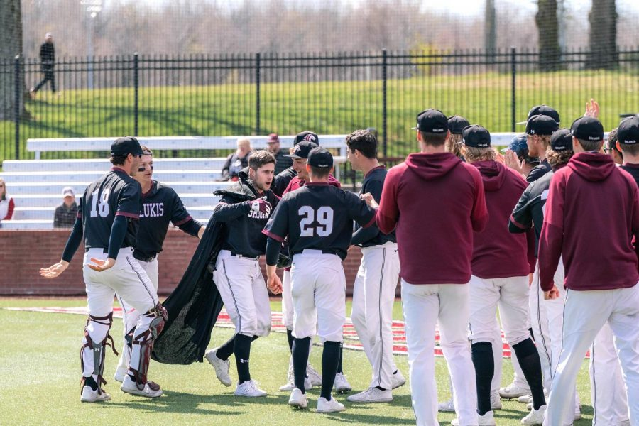 The Salukis rush to celebrate with Brad Hudson (4) in game three against University of Arkansas Sunday, March 28, 2021 at SIU. Hudson had just scored a home run.