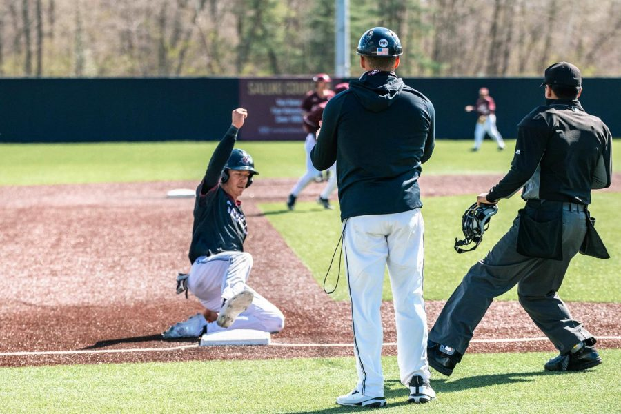 Nick Neville (9) slides into third base in game three against University of Arkansas Sunday, March 28, 2021 at SIU. Philip Archer (44) hit a single, allowing Neville to run home and score for the Salukis.