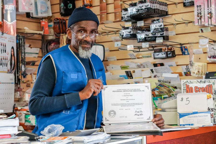 Abdul Rahim Khalil poses with his alcohol and other drug abuse counselor certification  Mar. 1, 2021, at Rahim's Beauty Supply in Carbondale, Ill. After being released from prison in 1993, Khalil opened his business and began studying at Southern Illinois University where he received a bachelor's degree in university studies and a master's degree in social work.