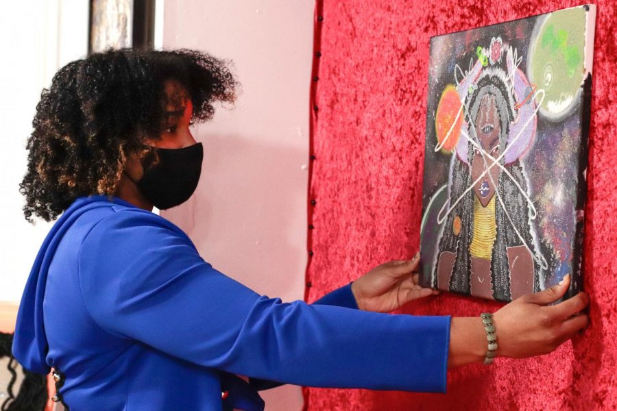 "Artist, A.J., hangs up her art, La Cosmodia, on a wall March 5, 2021, at Project Human X in Carbondale, Ill. ""It was made for Black History Month as part of Project Human X so it's meant to highlight, you know, the divine nature of Black women because I think that the world looks at Black women kind of like to be stereotyped as like angry or just mean or like whatever, but I think, like, the core thing that comes to my mind like when I picture a Black woman is just, like, nurturing, and when I think of nurturing, I think of space because space makes up everything,"" A.J. said."