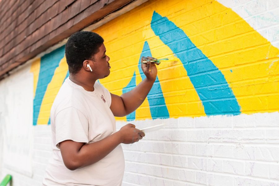 "Community activist and leader, Michael Coleman, paints the Art Reconciliation community mural March 5, 2021, in Carbondale, Ill. ""Just being able to just give time to give back to your community, I think that's really important. We take so much but, like, we have to keep giving back to the community and this is my way of doing it,"" Coleman said."