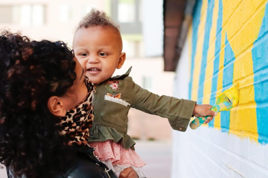 Cree Sahidah Glanz and Marquez Scoggin's daughter, Masterpeace, paints part of the Art Reconciliation community mural March 5, 2021, in Carbondale, Ill. Glanz said that art is for people of all ages and they like to expose Masterpeace to it for that reason.